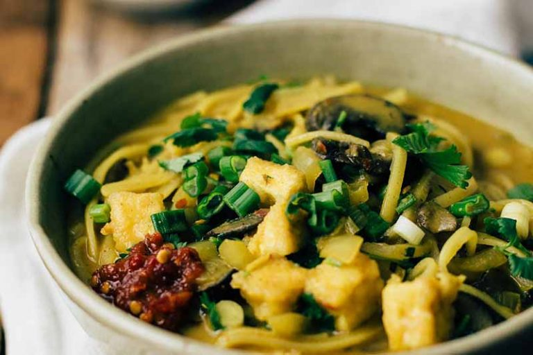 Horizontal image of a bowl of tofu and mushroom curry with fresh garnishes