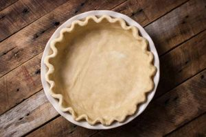 Horizontal image and top down view of a vegan pie crust in a pan sitting a rustic, dark, wooden table.