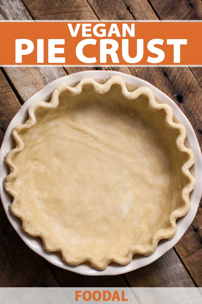 Top down and close up view of a vegan-friendly pie crust sitting in a white, glass pie pan on a dark, rustic wooden surface.