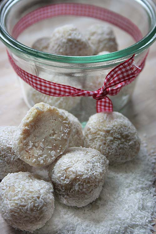 Vertical image of white chocolate truffles coated with shredded coconut, on a wood surface with a glass jar died with red and white checkered cloth ribbon.