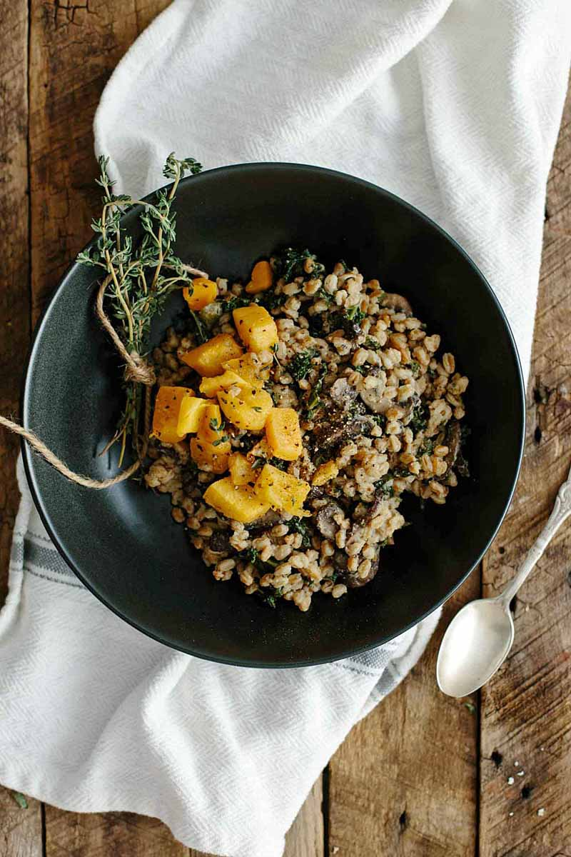 Top down view of a nonstick frying pan sitting on a white linen kitchen towel and rustic wooden table top. The skillet is full of a vegan Farro Risotto with Mushrooms & Kale dish. The skillet is sitting on a white linen towel and a rustic wooden table top. A sliver spoon lays to the lower right.