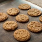 Oblique view of a batch of einkorn snickerdoodle cookies on a baking sheet.