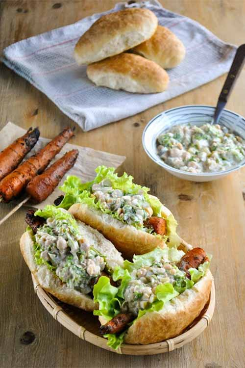 Barbecue carrot dogs with lettuce and chickpea salad, in a basket in the foreground, with three grilled carrots on sticks on a napkin, three hot dog buns on a folded kitchen towel, and a bowl of garbanzo salad with a spoon, on a wood surface.