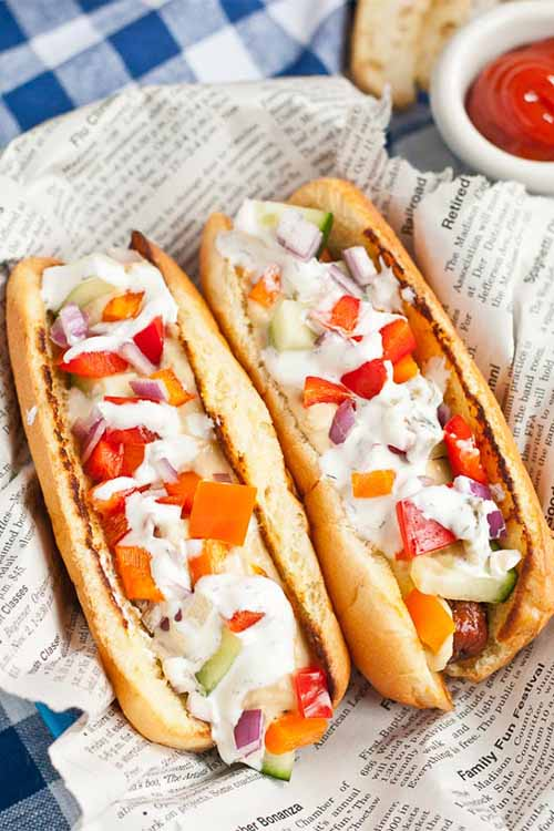 Two grilled franks topped with vegetables and tzatziki, on newspaper on top of a blue and white checkered cloth, next to a small white dish of ketchup.