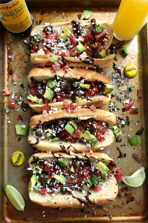 Overhead vertical image of four hot dogs with chopped avocado, crumbled cheese, and a drizzle of mole sauce, with a glass and a bottle of beer, two bottle caps, and lime wedges on a metal baking sheet.