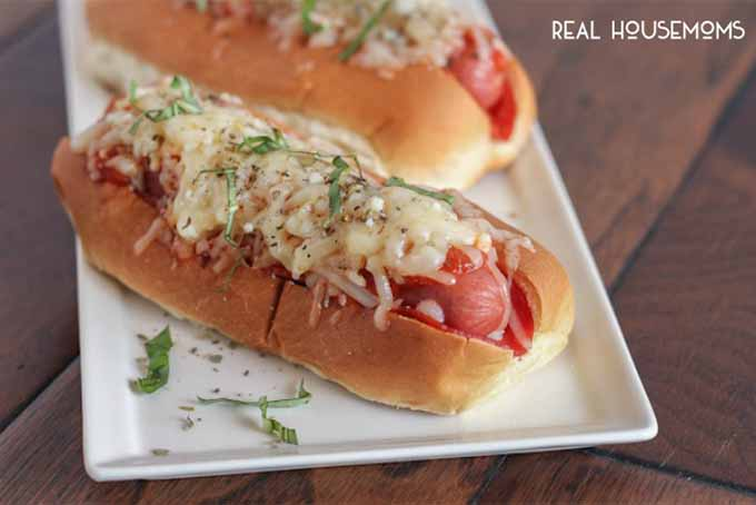 Pizza Hot Dogs topped with melted cheese and fresh herbs, on a white rectangular ceramic serving platter, on a brown wood surface.