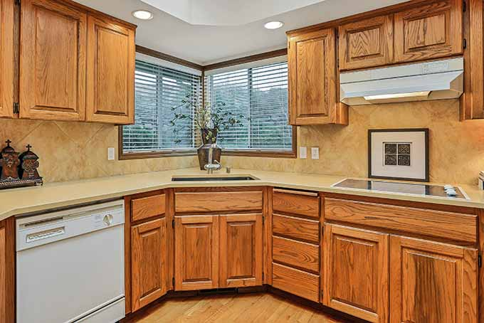 A kitchen with 90s-style light brown wood cabinets.