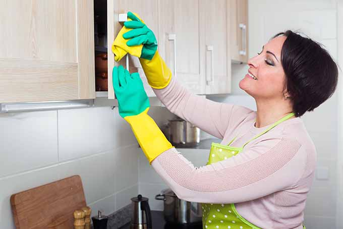 Woman Scrubbing Kitchen Cupboard Handles | Foodal.com