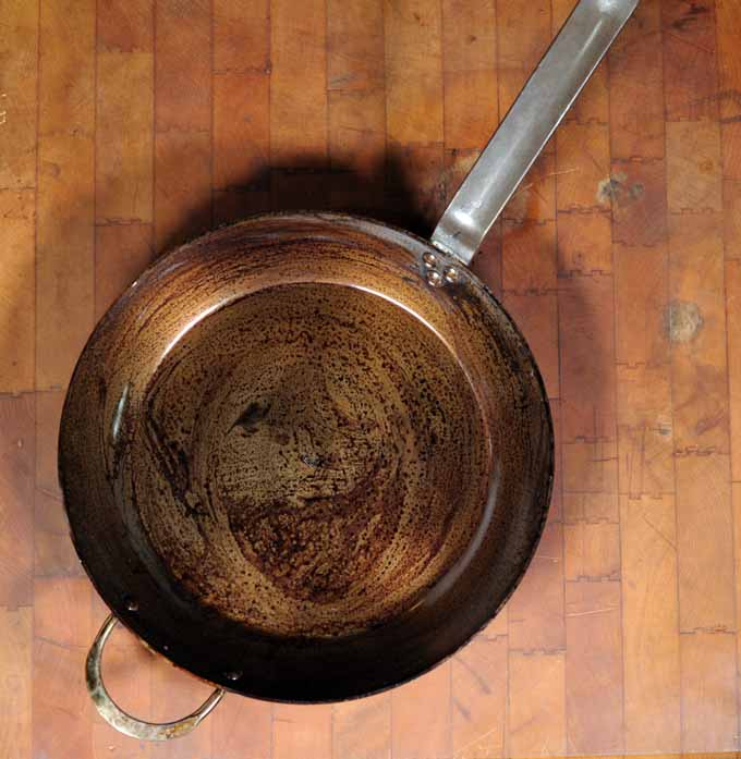 A DeBuyer Mineral B Element Iron Fry Pan that has been partially seasoned.