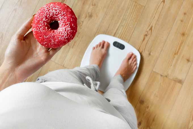 A woman holds a donut with here left hand while standing on a set of scales. | Foodal.com