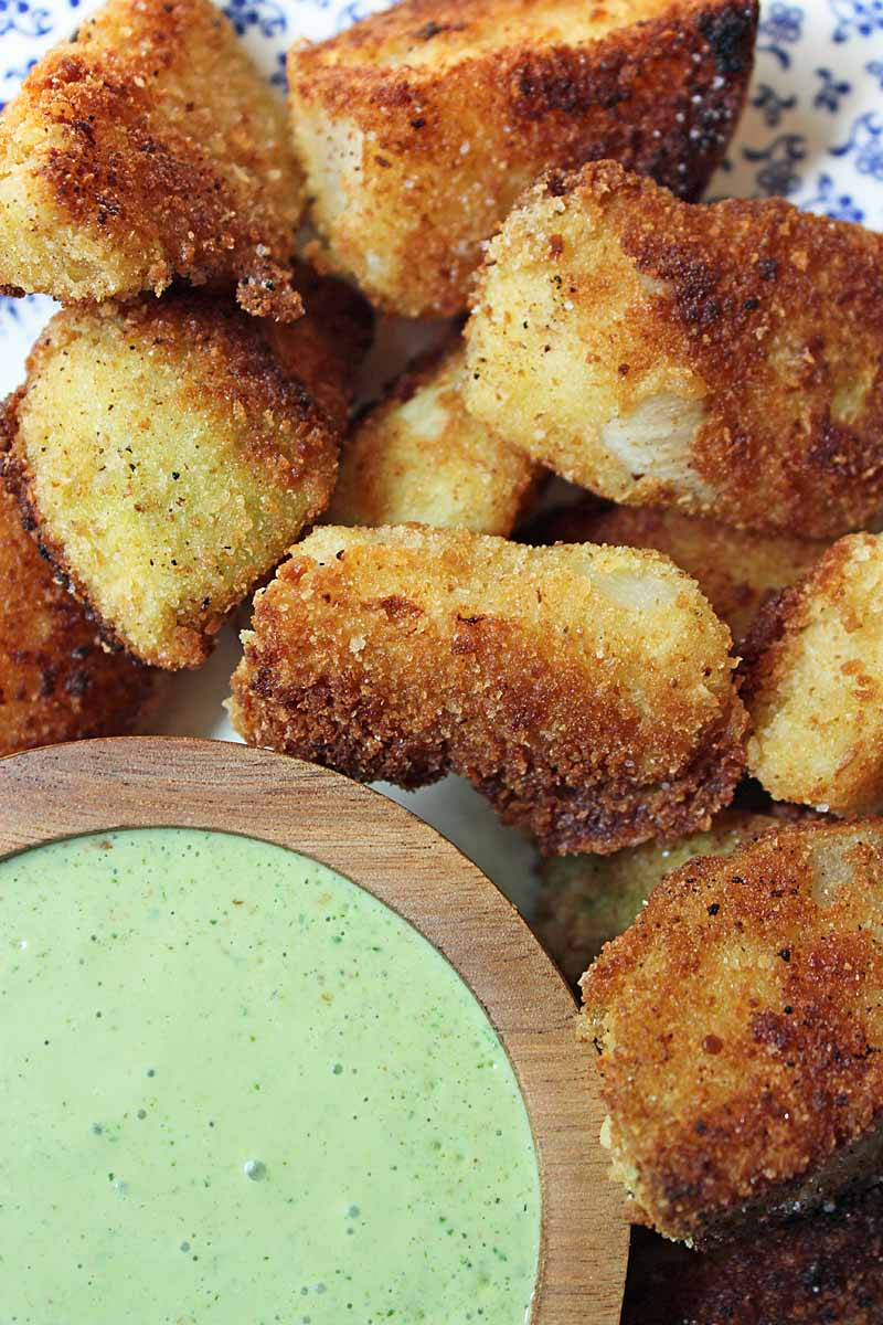 Top down view of a batch of fried kohlrabi wedges with a green dipping sauce made with cilantro and yogurt.