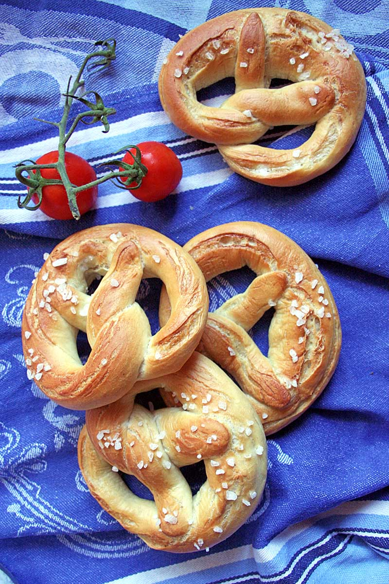 Top down view of four German soft lye pretzels on a medium cornflower blue table cloth. Two red cherry tomatoes in the upper left provide contrast against the blue.