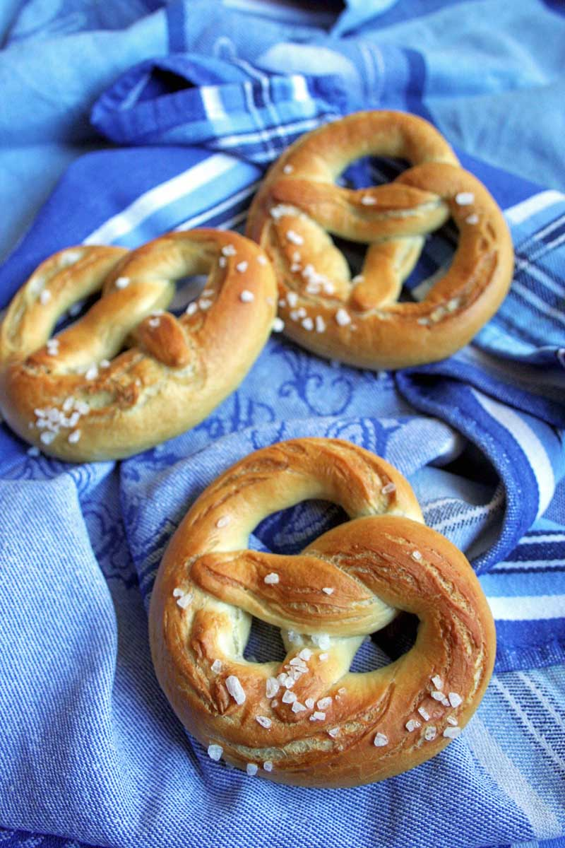 Slightly oblique top down view of three large German soft pretzels on a shimmery blue table cloth.