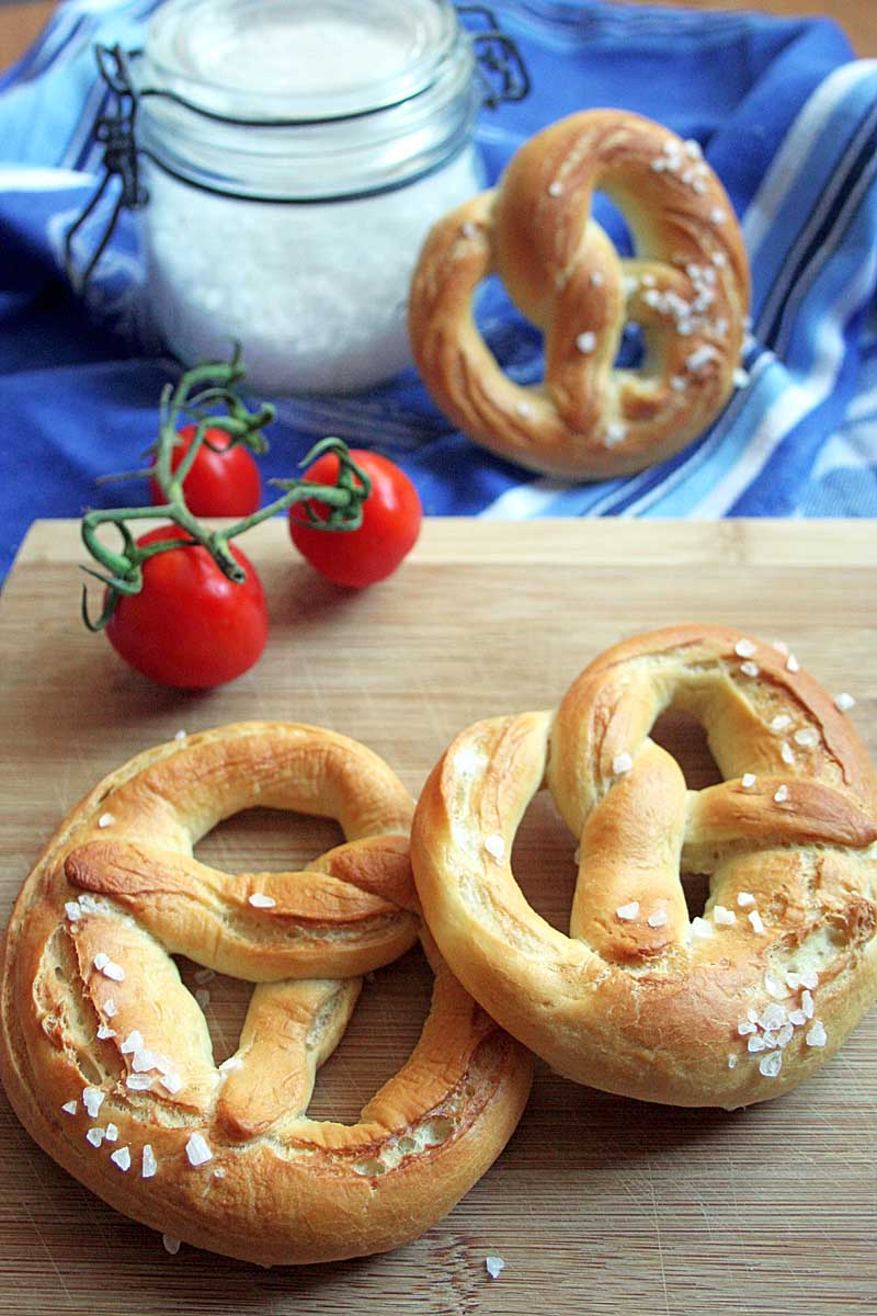 Oblique view of two German soft lye pretzels on a wooden cutting board with a jar of course salt and cherry tomatoes in the background.