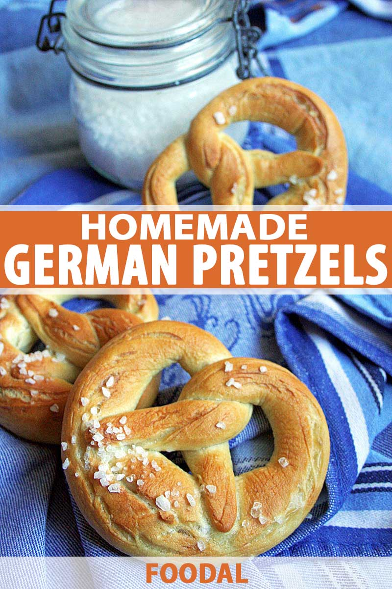 Oblique vie of German soft lye pretzels on a blue table cloth with a jar of coarse sea salt in the background.