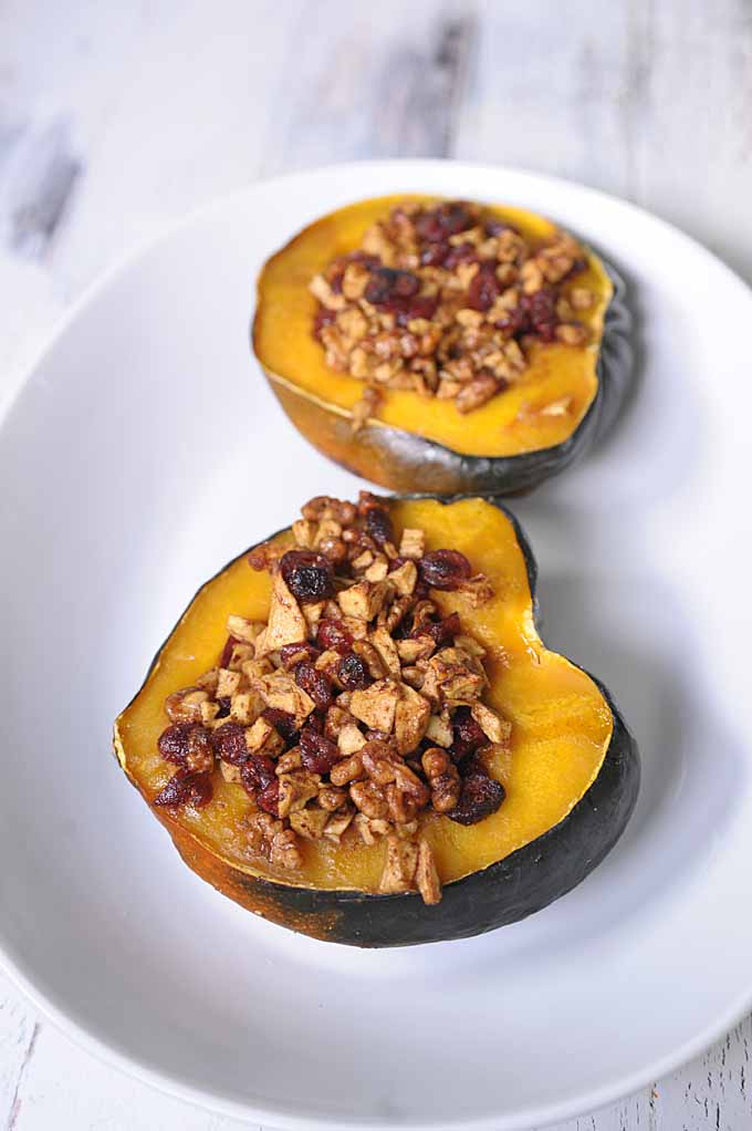 Oblique view of a white platter with two halves of acorn squash stuffed with walnuts, dried cranberries, apple chunks and sprinkled with cinnamon.