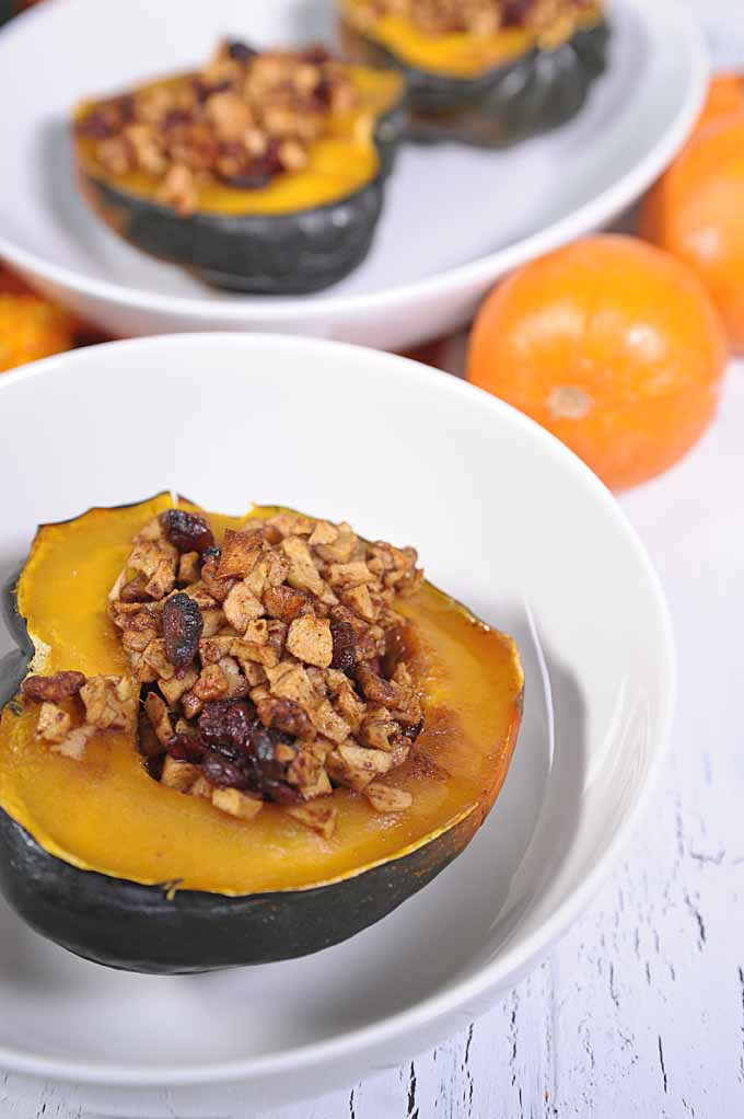 A stuffed acorn squash half in a white bowl in the foreground. Two other squash halves in an oval bowl along with mini pumpkins in the diffused background.