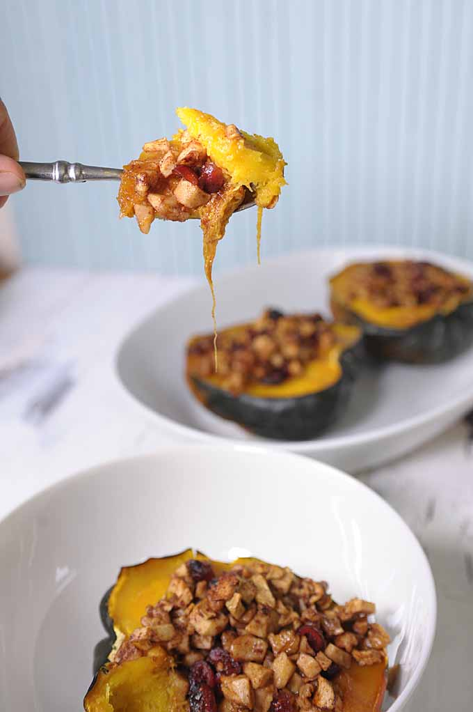A human hand raises a spoon full of baked acorn squash with apple chunks, dried cranberries, and walnuts.