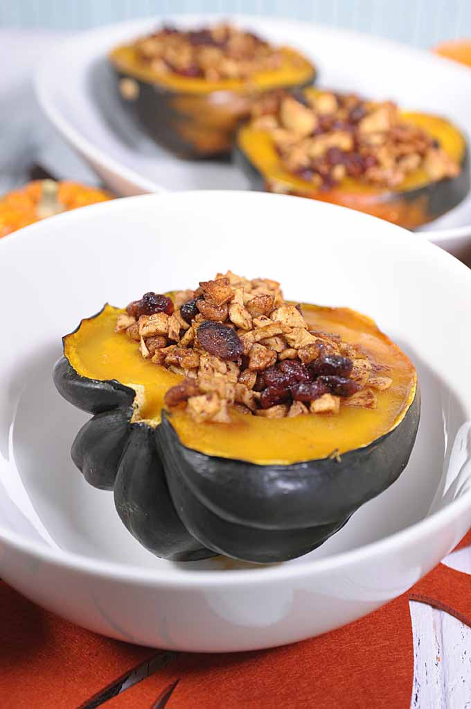 Oblique, close up view of a half of an acorn squash stuffed with apple pieces, walnuts, dried cranberries and then baked. Sitting in a white porcelain bowl. Bowl is sitting on place mats shaped and colored like autumn leaves. Two others are in a diffused background.