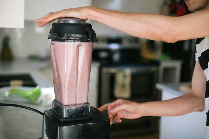 A man makes Pomegranate Melon Apple Aloe Juice in a Vitamix Blender.
