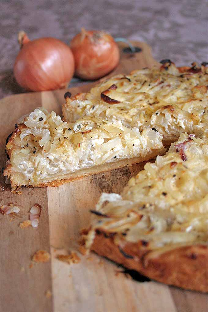 An oblique view of a German-Style Onion Tart with several slices removed. Two yellow onions are in a diffused background.