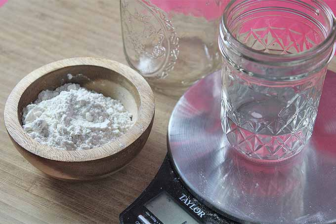 A small wooden bowl of flour, a glass mason jar, and a jelly jar of water being weighed on a kitchen scale, on a wooden board.