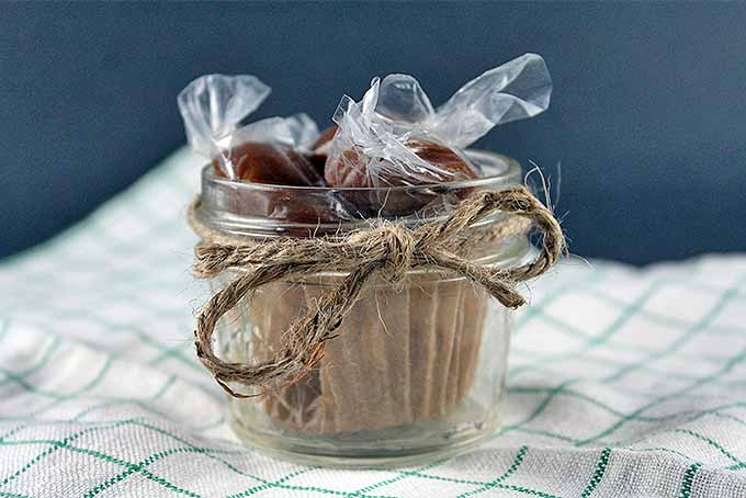 Horizontal closeup image of plastic-wrapped homemade caramel candies in small glass jar lined with brown paper and tied with twine, on a green and white checkered cloth, with a blue-gray background.