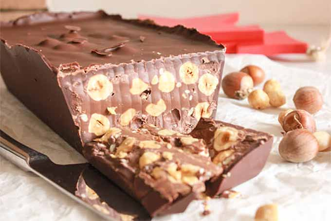 Homemade chocolate torrone with hazelnuts, with a few pieces that have been cut with a knife, on a white surface with whole and shelled nuts.