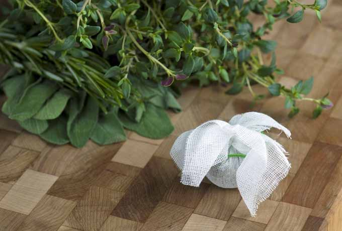 Bouquet Garni on a wooden chopping block | Foodal.com