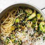Top down view of bowl full of spaghetti noddles topped with shaved Brussels sprouts, leeks and pine nuts.