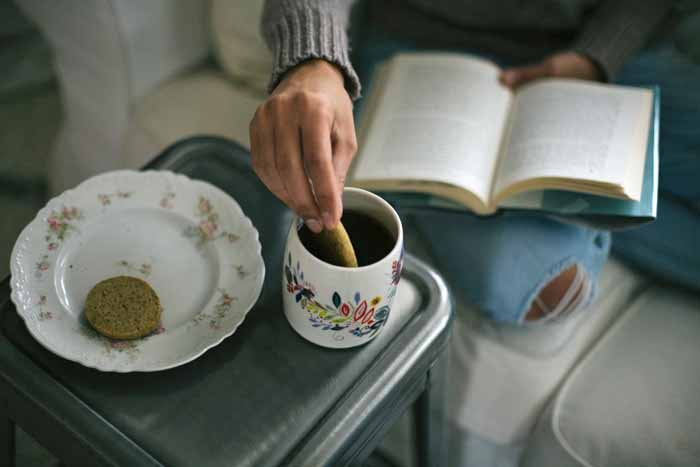 A man with a book on his lap dips his Earl Grey Einkorn cookie into a cup of tea.