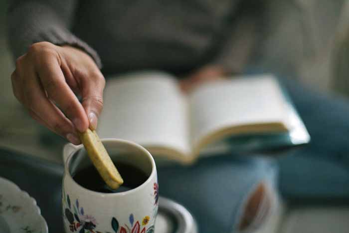 A man with a hardcover book on a his lap dunks a einkorn Earl Grey cookie into a cup of tea.