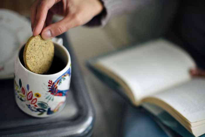 A human hand dunks a einkorn Earl Grey cookie into a cup of tea.