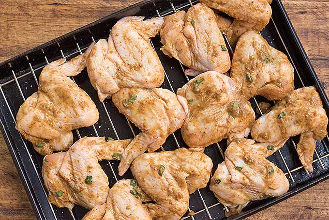 Chicken wings coated with a simple spicy marinade, arranged on a baking pan and ready to go in the oven. | Foodal.com