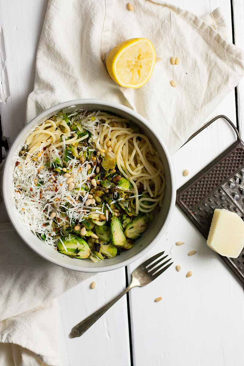 Top down view of a white ceramic bowl full of pasta with shaved Brussels sprouts, leeks, and pasta siting on a white, linen table cloth. A half a lemon sits above the bowl and a fork below it.,