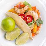 Homemade shrimp fajita topped with cilantro and red jalapeno slices, and a squeeze of lime. | Foodal.com