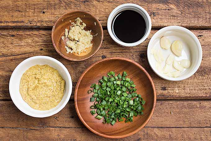 All of the ingredients required to make a simple spicy wing marinade, including Dijon mustard, garlic, ginger, scallions, and soy sauce. | Foodal.com