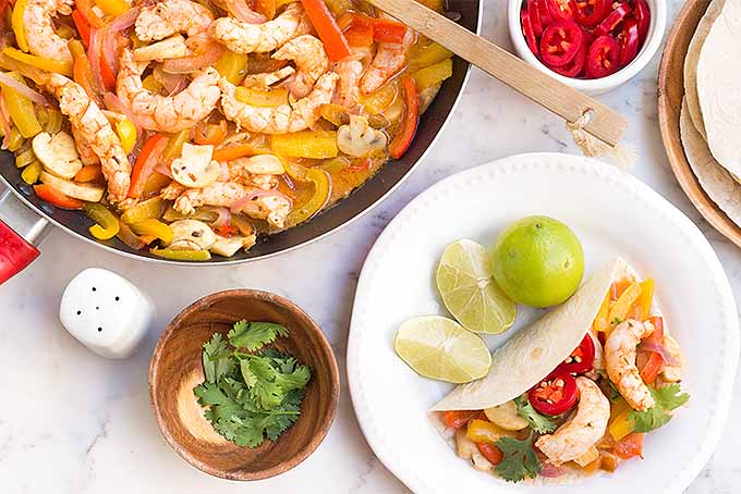 Homemade shrimp fajitas with sauteed bell pepper, mushrooms, and onions, served in flour tortillas with sliced jalapeno and cilantro. | Foodal.com