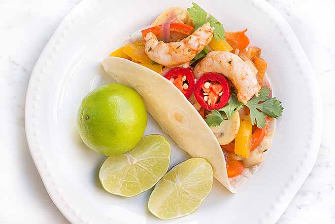 Tortillas filled with marinated shrimp and sauteed fresh vegetables, topped with jalapeno slices, cilantro, and lime. | Foodal.com