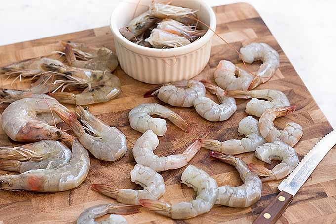 Devein and butterfly extra-large shrimp but leave the tails on for a delicious buttery baked scampi. | Foodal.com
