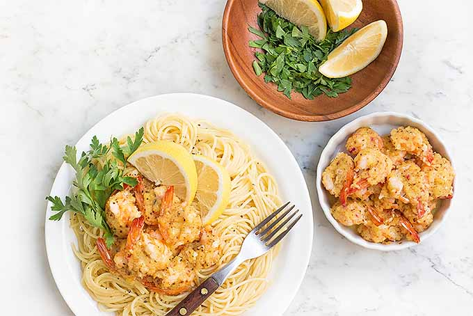 Enjoy a bowl of pasta topped with classic buttery baked shrimp scampi, with parsley and lemon for garnish. | Foodal.com