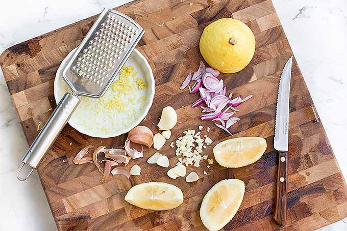 Prep minced garlic and purple shallots, lemon juice and zest to make classic buttery baked shrimp scampi at home. | Foodal.com