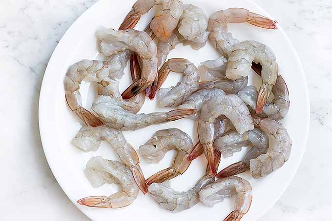 Devein and and butterfly whole, raw shrimp but leave the tails on for our classic buttery baked shrimp scampi recipe. | Foodal.com