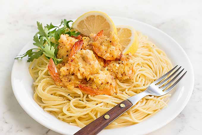 What's for dinner? A delicious and satisfying plate of spaghetti topped with buttery baked shrimp scampi. | Foodal.com
