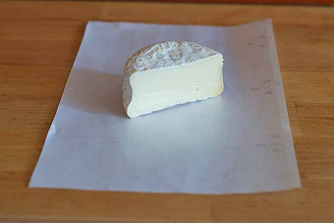 A wedge of cheese before it's wrapped up in paper | Foodal.com