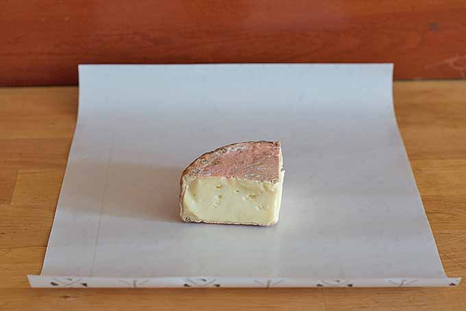 Getting ready to wrap a wedge of cheese in paper | Foodal.com