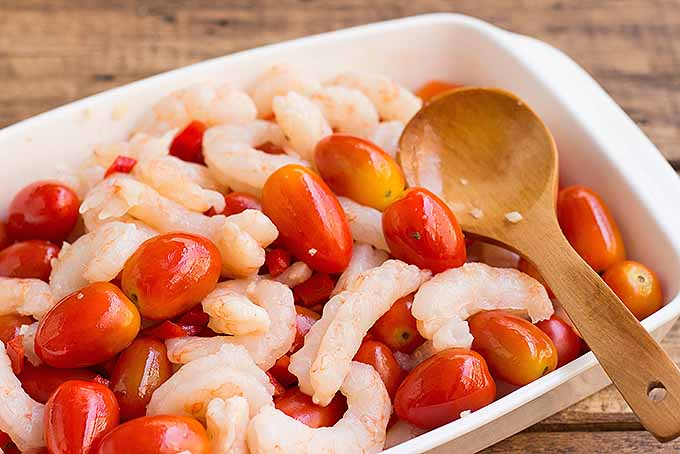 Mixing together shrimp and roasted cherry tomatoes for a quick and healthy meal | Foodal.com