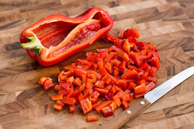 Cutting the peppers to add flavor and texture to our recipe for roasted tomatoes with shrimp and feta cheese | Foodal.com