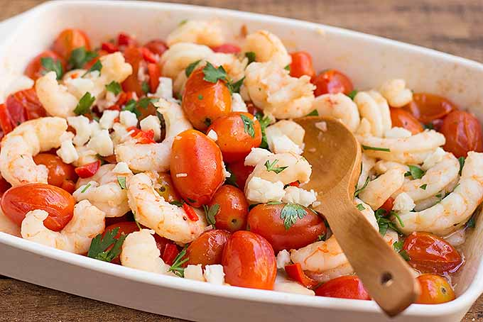 Mixing together roasted tomatoes, shrimp, and feta cheese | Foodal.com