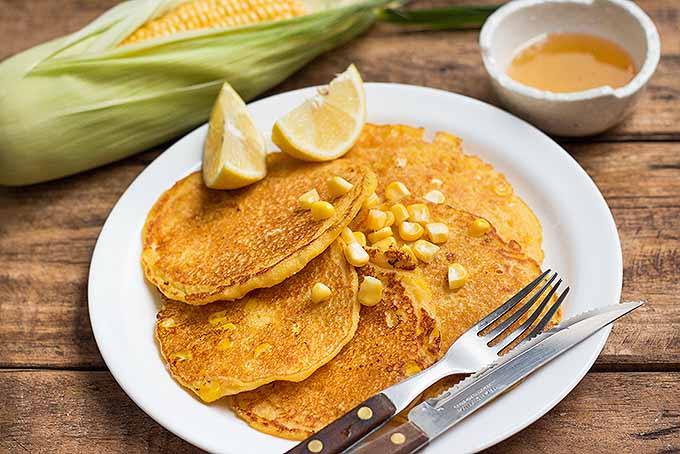 Enjoying a plateful of sweet cornmeal pancakes made with fresh corn. | Foodal.com
